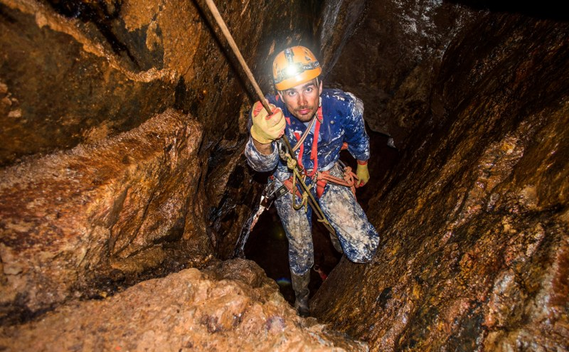 Mine explorer using SRT to climb a rope in a mineshaft in Cornwall.