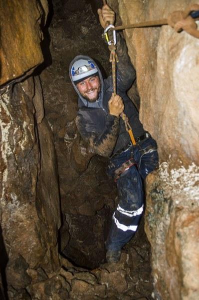 Mine explorer traversing a deep mine shaft near St. Ives, Cornwall.