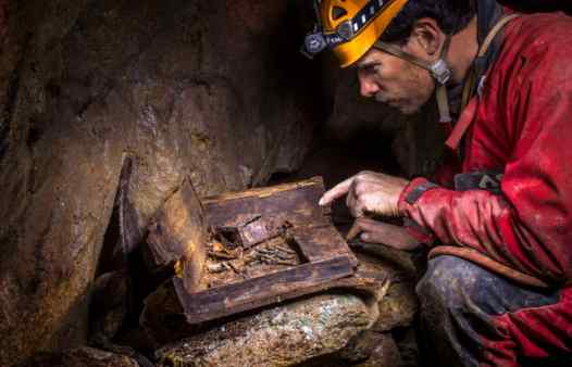Underground artefacts in a Cornish tin mine. Mine explorer examines a box of fuses near St. Just