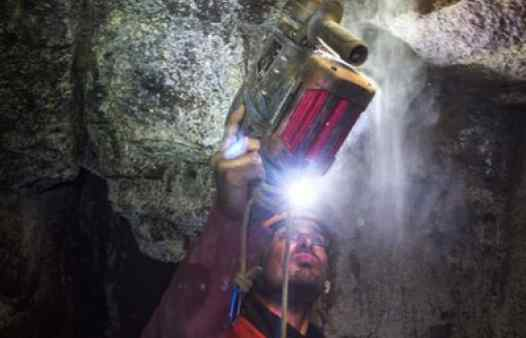 Cornwall Underground Adventure guide bolting an abseil anchor in a Cornish tin mine
